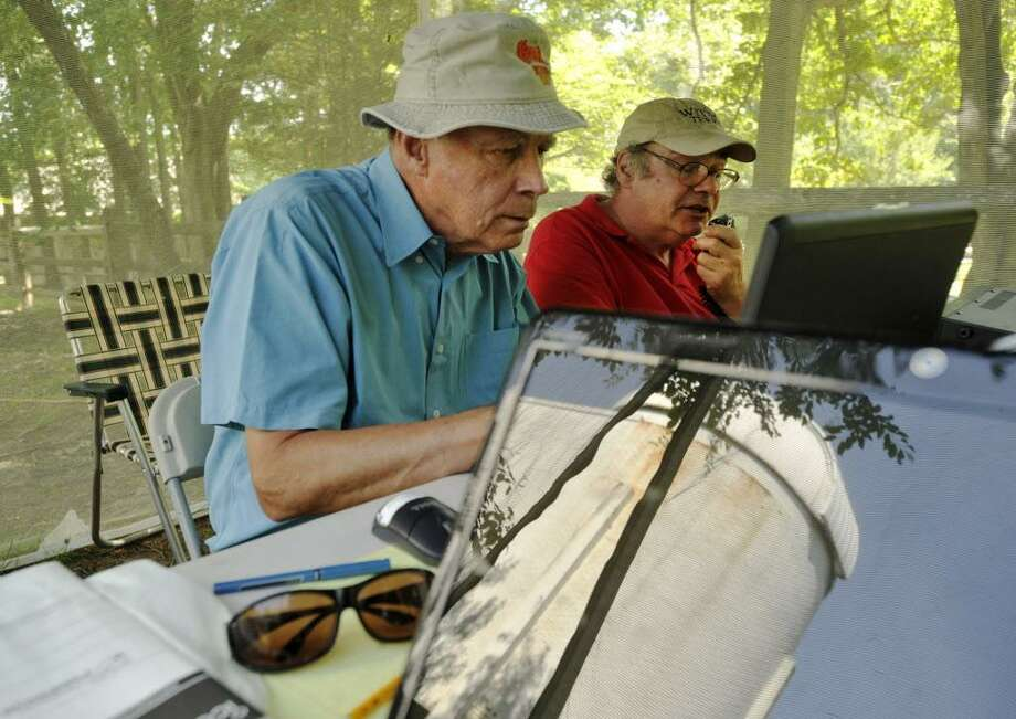 Tom Young, left, and Terry Martin attempt to make contact with another ham radio operator with the Stamford Observatory reflected on a computer screen during the Stamford Amateur Radio Association's field day at the Stamford Museum & Nature Center on Sunday, June 23, 2013. Photo: Jason Rearick / Jason Rearick / Stamford Advocate