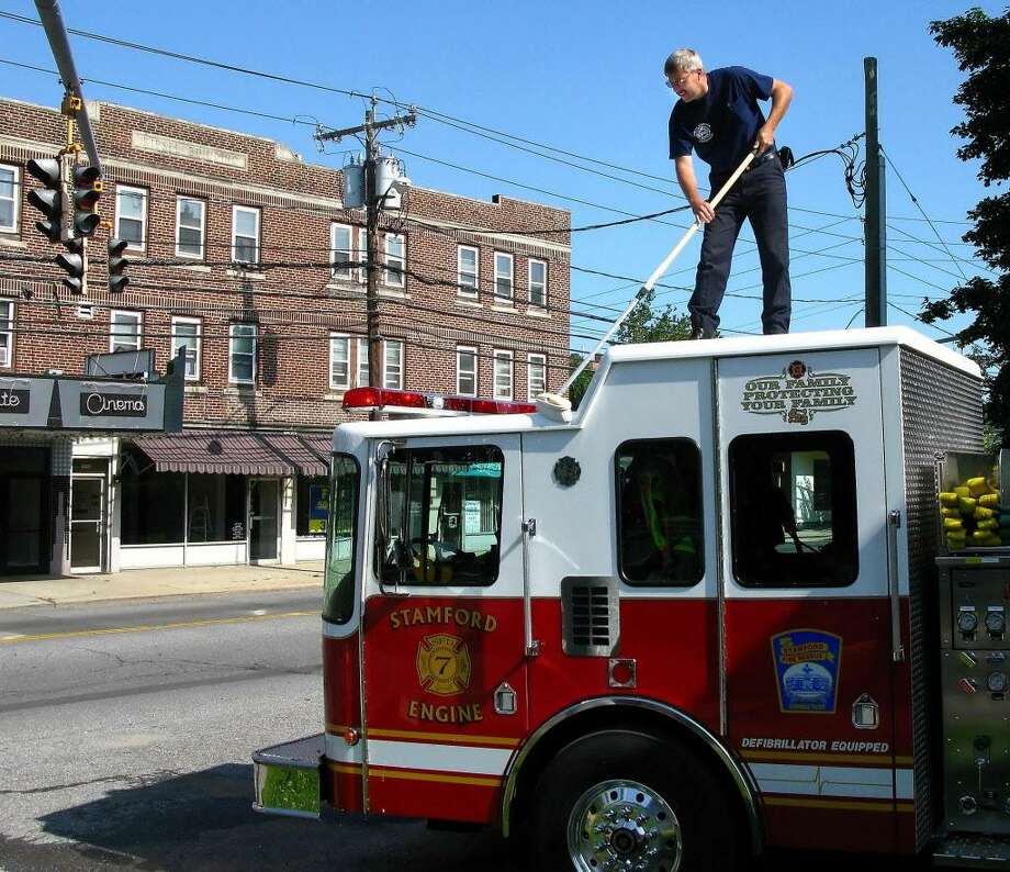 7-13-2009, HOPE STREET, STAMFORD, Stamford firefighter, Ken Riordan, of Stamford Fire & Rescue Engine 7,  scrubs down the top of Engine 7 Monday morning outside the firehouse on Hope Street.  Bob Luckey/Staff Photo Photo: ST