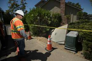 Jason Amerine, with PG&E Traffic Control, looks at the lid of a splice box, weighing hundreds of pounds was lifted askew at 6 a.m. when it failed due to the hot weather affecting more than 5000 customers at the peak of the outage according to PG&E spokesperson Tamar Sarkissian on S. Larwin and Wildberry Court on Tuesday, June 20, 2017 in Concord, CA.