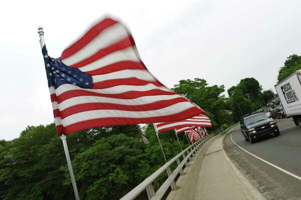 American flags blow in the wind as traffic passes over the Route 1 Mianus River Bridge in Greenwich, Conn. Thursday, July 2, 2015.