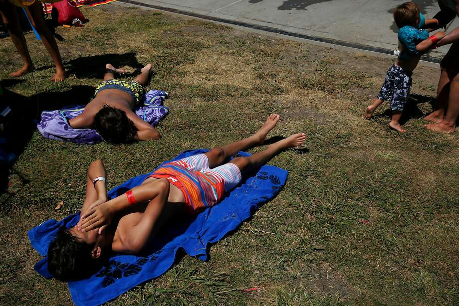 Julian Schmilinsky, 13, lower left, wipes sweat from his face while laying in the sunshine with John-Paul Schmilinsky, 12, upper left, while Heather Mu–oz, far right, picks up her son Leo, 2, as they wait to get back into the Contra Loma Swim Lagoon in the 100 degree heat June 21, 2017 in Antioch, Calif. Photo: Leah Millis, The Chronicle