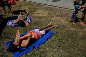 Julian Schmilinsky, 13, lower left, wipes sweat from his face while laying in the sunshine with John-Paul Schmilinsky, 12, upper left, while Heather Mu�oz, far right, picks up her son Leo, 2, as they wait to get back into the Contra Loma Swim Lagoon in the 100 degree heat June 21, 2017 in Antioch, Calif.