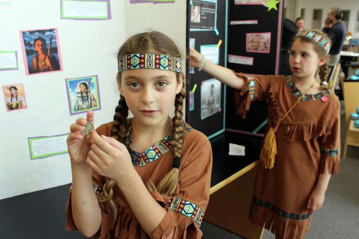 Lainey Kovach shows the Sacagawea dollar as part of her presentation at Cider Mill's Living Museum on Wednesday, June 21, 2017. Alison Royle, who is behind her, also dressed up as Sacagawea.