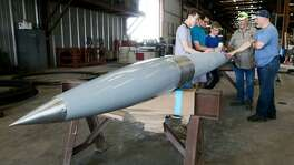 Theodore Gleinser (from left), Eric Anderson and Drew Yockey, all 18, with the Alamo Heights rocket program, put the finishing touches on their 20-foot, six-inch 600-pound rocket with the help of Gary Gates and Aerospace Science teacher Colin Lang at Gates Machine & Fabrication, 8025 Jethro Lane, on Wednesday, June 21, 2017. The rocket is dedicated to a former student, Blake Duckers, who died unexpectedly at his home in Seattle this year and who was in the inaugural class of the rocketry program in 2012. The rocket will attempt to carry a 35 pound payload, including a piece of that first rocket, to a height of 100,000 feet while traveling at a speed of Mach 3, three times the speed of sound. It will be launched at the White Sands Missile Range in New Mexico on June 28. MARVIN PFEIFFER/mpfeiffer@express-news.net