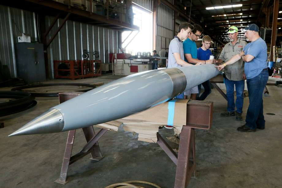 Theodore Gleinser (from left), Eric Anderson and Drew Yockey, all 18, with the Alamo Heights rocket program, put the finishing touches on their 20-foot, six-inch 600-pound rocket with the help of Gary Gates and Aerospace Science teacher Colin Lang at Gates Machine & Fabrication, 8025 Jethro Lane, on Wednesday, June 21, 2017. The rocket is dedicated to a former student, Blake Duckers, who died unexpectedly at his home in Seattle this year and who was in the inaugural class of the rocketry program in 2012. The rocket will attempt to carry a 35 pound payload, including a piece of that first rocket, to a height of 100,000 feet while traveling at a speed of Mach 3, three times the speed of sound. It will be launched at the White Sands Missile Range in New Mexico on June 28. MARVIN PFEIFFER/mpfeiffer@express-news.net Photo: Marvin Pfeiffer /San Antonio Express-News / Express-News 2017