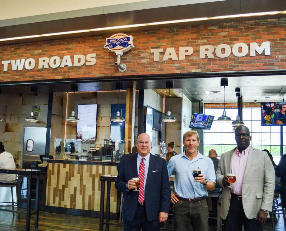 From left to right: Kevin A. Dillon, A.A.E., Executive Director of the Connecticut Airport Authority; Brad Hittle, CEO and Co-Founder of Two Roads Brewing Company; and Tyrone Davis, Senior Director of Operations at The Michell Group, celebrate the opening of the new Two Roads Tap Room at Bradley International Airport. Photo: Contributed Photo /Connecticut Post