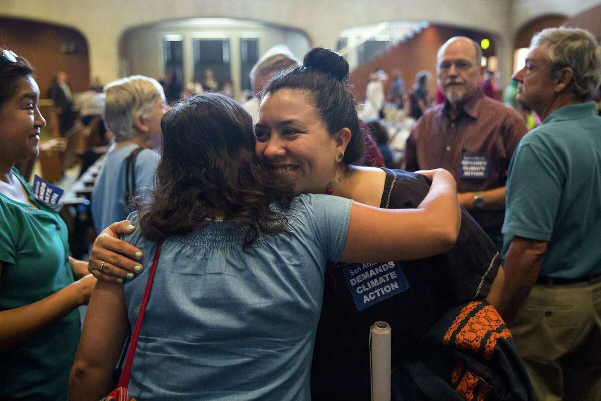 Jessica O. Guerrero, center, embraces a fellow Vecinos de Mission Trails member after the city council passed a resolution in support of the Paris Climate Agreement during a city council meeting at the Municipal Plaza building in San Antonio, Texas on June 22, 2017. Ray Whitehouse / for the San Antonio Express-News
