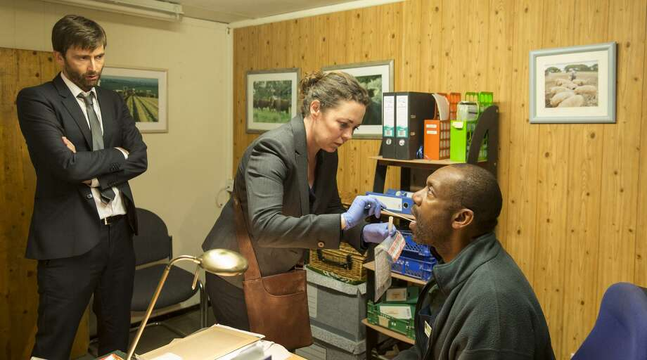 """Detectives Hardy (David Tennant, left) and Miller (Olivia Colman) get a DNA sample from Ed (Lenny Henry) in """"Broadchurch."""" Photo: Colin Hutton / Colin Hutton / Kudos/Imaginary Friends/Sister Pictures/ITV"""