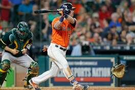 HOUSTON, TX - APRIL 28:  Josh Reddick #22 of the Houston Astros reaches base as Stephen Vogt #21 of the Oakland Athletics is called for catcher interference as his glove strikes the bat in the fourth inning at Minute Maid Park on April 28, 2017 in Houston, Texas.  (Photo by Bob Levey/Getty Images)