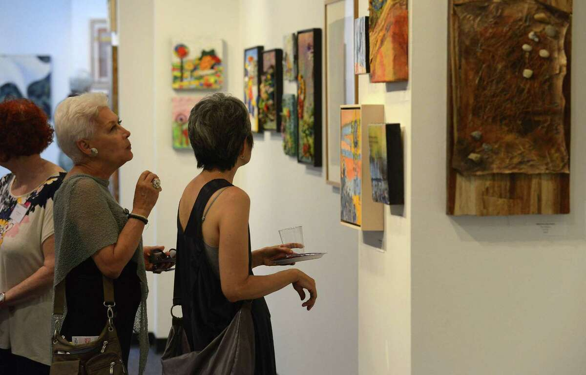 FILE - Patrons take in artwork of local artist being displayed at UCONN Gallery during the 4th annual ARTWALK in Stamford Downtown on Friday, June 24, 2016.