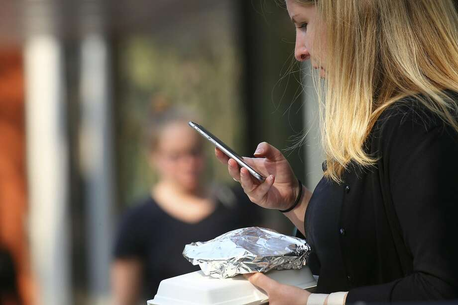 "FILE – A woman checks her mobile device while walking on University Avenue in Palo Alto, Calif., on Sept. 19, 2016. A former Senate candidate from California reportedly left voicemails detailing his plans to establish a ""regional capital"" in North Idaho.  Photo: JIM WILSON, NYT"