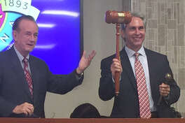 Pasadena Mayor Johnny Isbell, left, passes the gavel to City Councilman Jeff Wagner, the mayor-elect.