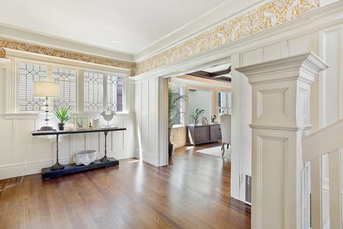 Tall wainscoting and a high ceiling defines this parlor area off the foyer.