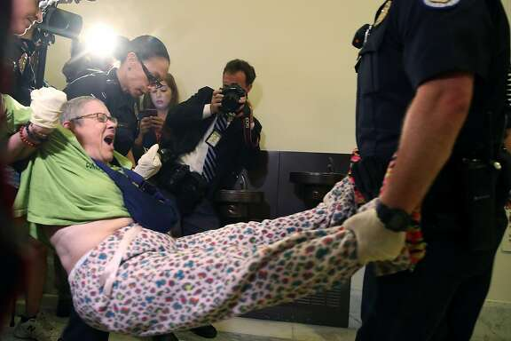 WASHINGTON, DC - JUNE 22:  U.S. Capitol Police remove a woman from a protest in front of the office of Senate Majority Leader Mitch McConnell (R-KY) inside the Russell Senate Office Building on Capitol Hill, on June 22, 2017 in Washington, DC. Members of a group with disabilities were protesting the proposed GOP health care plan that was unveiled today.  (Photo by Mark Wilson/Getty Images)