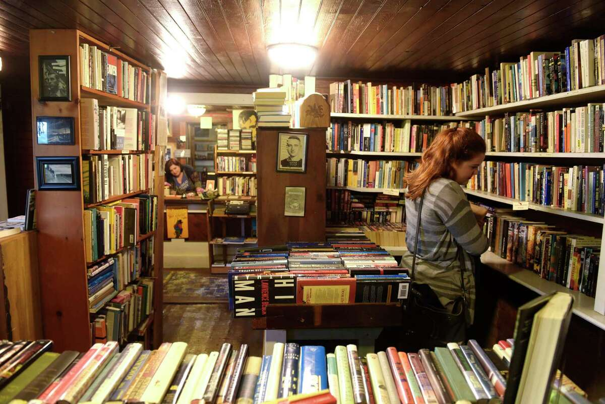 Emily Martin of Albany, right, searches through the books at Down in Denver Books, as owner Louise Hendry, background, works at the counter on Tuesday, June 6, 2017, in Stephentown, N.Y. Martin who was on her way to The Clark museum saw the store as she drove by and turned around to come in a shop.