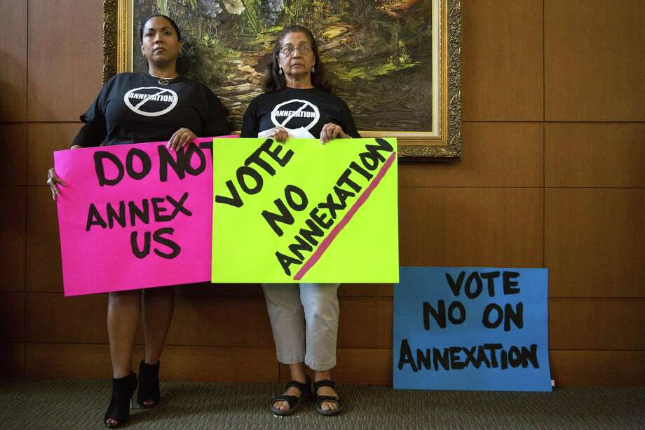 Lucy Adame-Clark (left) and Molly Martinez hold up signs against annexation at a City Council meeting Thursday. Photo: Ray Whitehouse /For The San Antonio Express-New