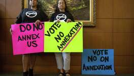Lucy Adame-Clark (left) and Molly Martinez hold up signs against annexation at a City Council meeting Thursday.