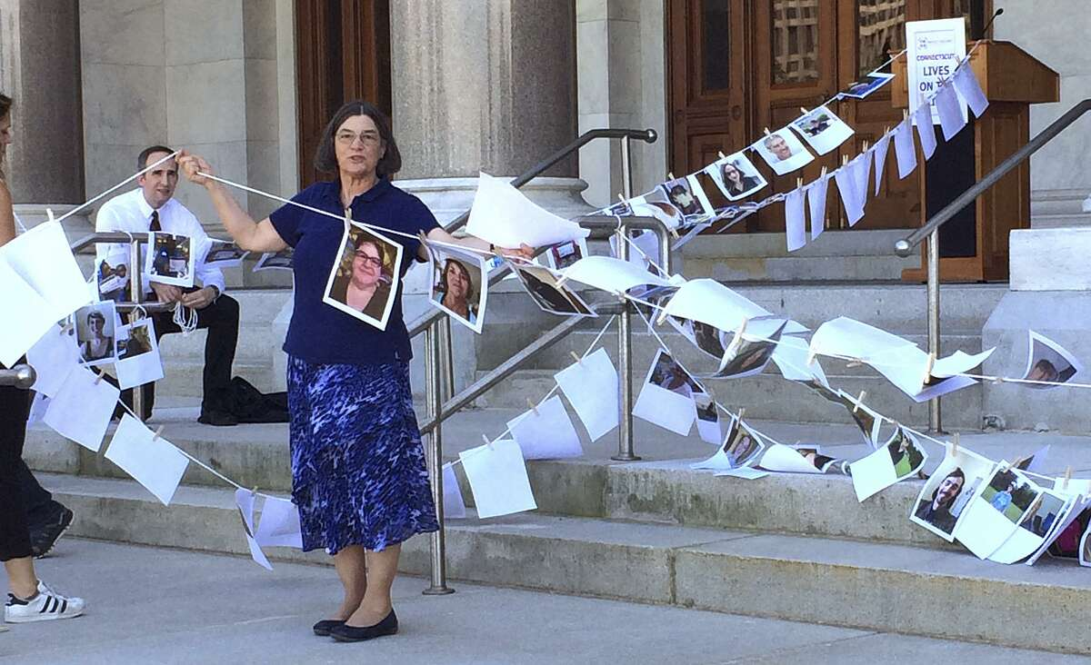 Jane McNichol, an organizer of the Protect Our Care CT campaign, holds up a clothesline with photos of Connecticut residents opposed to repeal of the Affordable Care Act, during a rally on the state Capitol steps, Thursday, June 22, 2017, in Hartford, Conn. The group gathered to demonstrate their position that Connecticut lives are