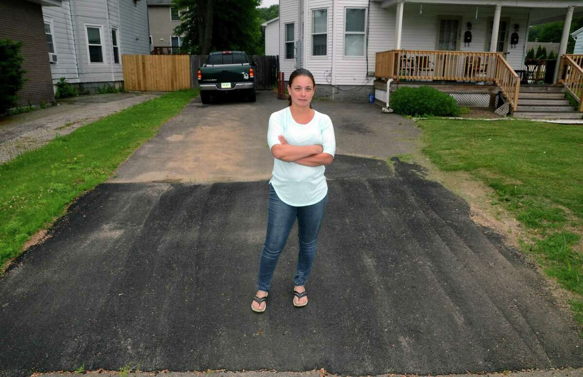 Crystal Jaumann stands atop her driveway on Wakelee Avenue which she said was shoddily patched last fall after Eversource Energy installed new natural gas lines under the road. .