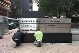 Workers install signage for Indigo Resources outside JPMorgan Chase Tower in downtown Houston Thursday, June 22, 2017.