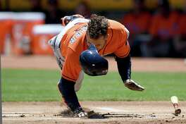 OAKLAND, CA - JUNE 22:  George Springer #4 of the Houston Astros falls to the ground after he was hit in the hand by a pitch from Jesse Hahn #32 of the Oakland Athletics in the top of the first inning at Oakland Alameda Coliseum on June 22, 2017 in Oakland, California.