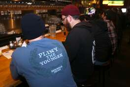 Emil Hanke Jr. (left) wears a shirt from last year's release of Pliny the Younger India Pale Ale at the Russian River Brewing Company in Santa Rosa, Calif. on Friday, Feb. 6, 2015. Beer lovers from across the country wait in long lines for a shot of sipping the IPA, listed at 10.25% ABV, during its 2-week limited availability.