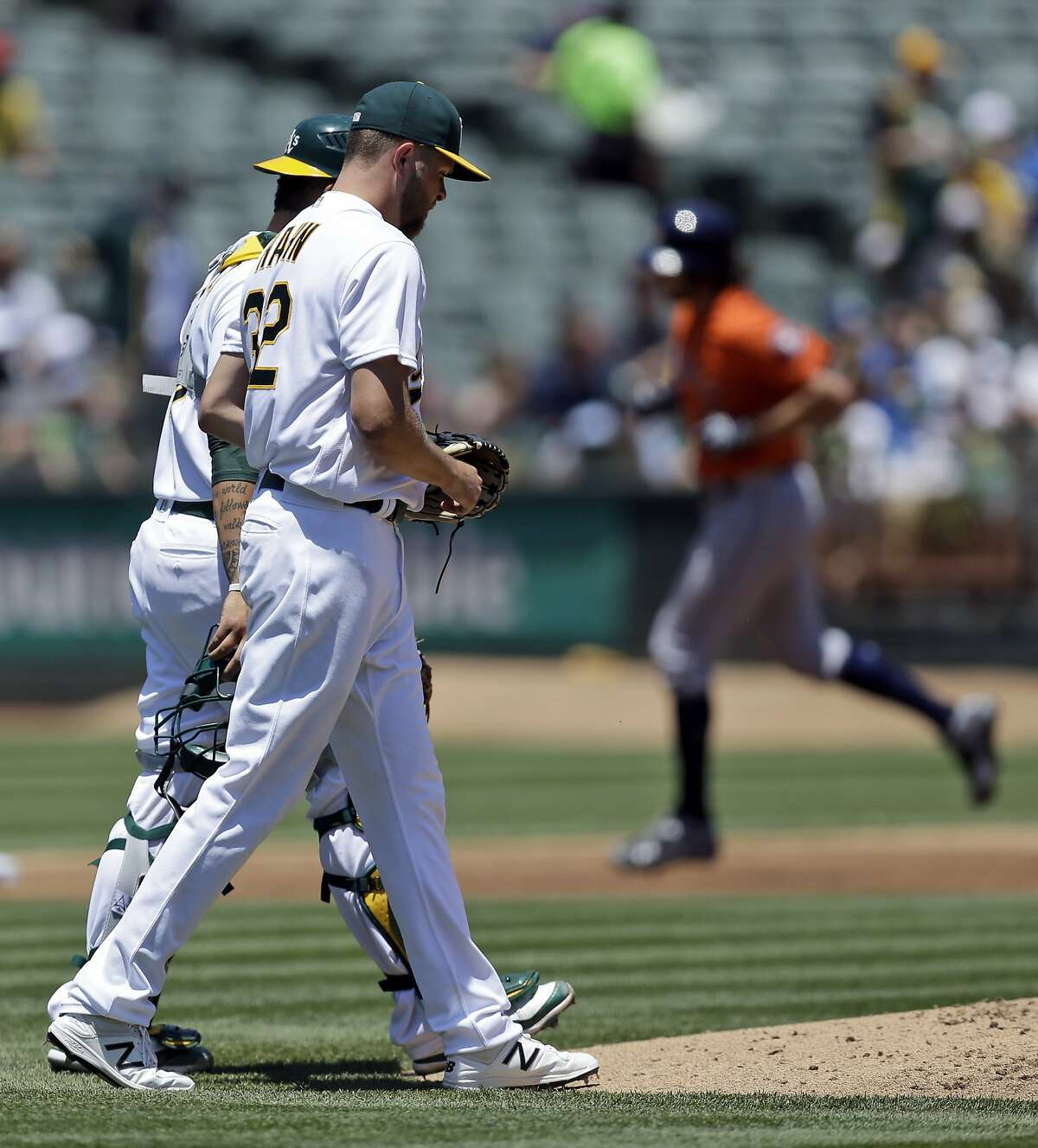 Oakland Athletics pitcher Jesse Hahn, left, walks back to the mound with catcher Bruce Maxwell as Houston Astros' Jake Marisnick, right, runs the bases after hitting a three-run home run off Hahn in the first inning of a baseball game Thursday, June 22, 2017, in Oakland, Calif. (AP Photo/Ben Margot)