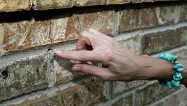 Barbara Brown points to a one of several cracks on an exterior wall of her home,  Saturday, June 21, 2014, in Reno, Texas. Brown said that she believes the cracks to her homes foundation and wall as related to the natural gas drilling in the area. (AP Photo/Tony Gutierrez)