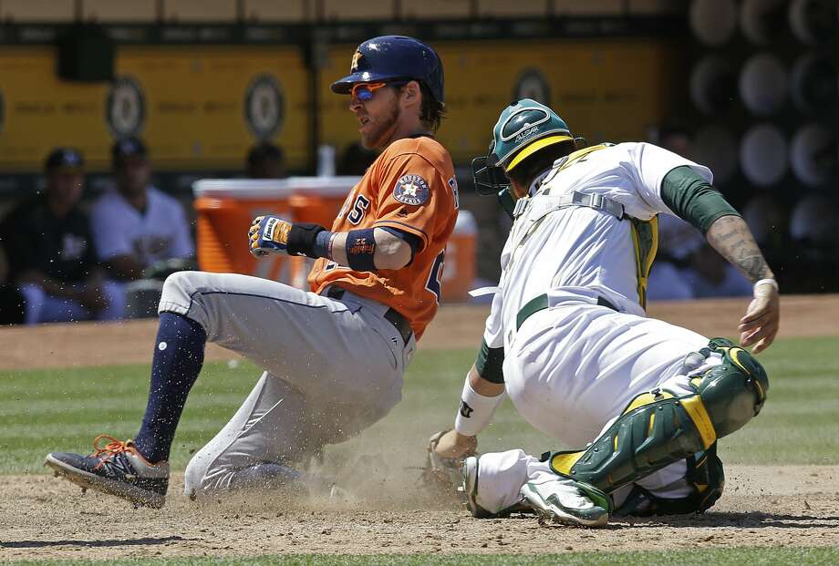 Houston Astros' Josh Reddick, left, slides to score behind Oakland Athletics catcher Bruce Maxwell during the eighth inning of a baseball game Thursday, June 22, 2017, in Oakland, Calif. (AP Photo/Ben Margot) Photo: Ben Margot/Associated Press