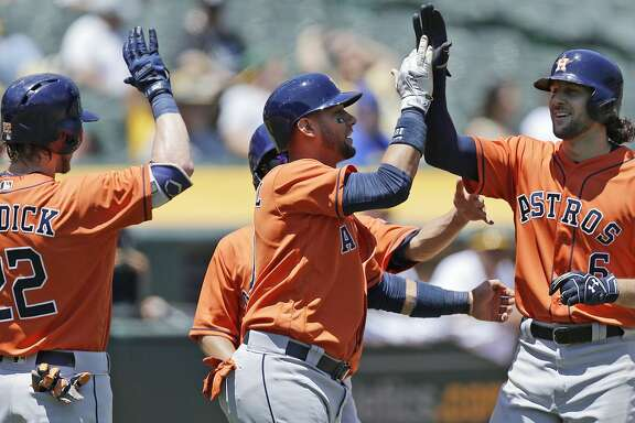 Houston Astros' Jake Marisnick, right, is congratulated by Josh Reddick (22) and Yuli Gurriel, center, after hitting a three-run home run off Oakland Athletics pitcher Jesse Hahn in the first inning of a baseball game Thursday, June 22, 2017, in Oakland, Calif. (AP Photo/Ben Margot)