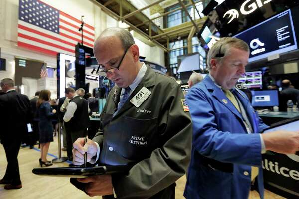 Traders Andrew Silverman, left, and James Lamb work on the floor of the New York Stock Exchange, Thursday, June 22, 2017. (AP Photo/Richard Drew)