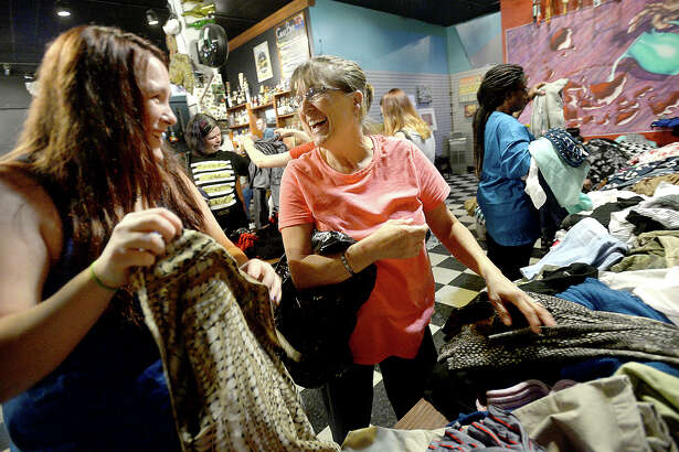 Destiny Hebert (left) and her mother Karla Somers joke with one another as they pour through the tables heaped with clothing items during the Beaumont City-Wide Clothing Swap Thursday at the Logon Cafe. Attendees were encouraged to bring donated items no longer being used and all were free to pick up as many new pieces as desired in exchange. The popular event offers clothing for men, women, and children, as well as accessories and household items. Photo taken Thursday, June 22, 2017 Kim Brent/The Enterprise