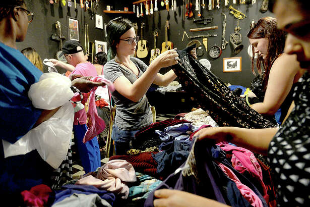 Courtney Jones checks out a garment as she and others pour through the tables heaped with clothing items during the Beaumont City-Wide Clothing Swap Thursday at the Logon Cafe. Attendees were encouraged to bring donated items no longer being used and all were free to pick up as many new pieces as desired in exchange. The popular event offers clothing for men, women, and children, as well as accessories and household items. Photo taken Thursday, June 22, 2017 Kim Brent/The Enterprise