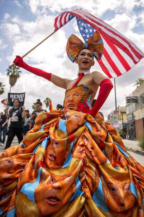 Khuong Lam wears a dress he made covered with faces of President Trump at this month's #ResistMarch during the 47th annual L.A. Pride Festival. Photo: David McNew, Getty Images