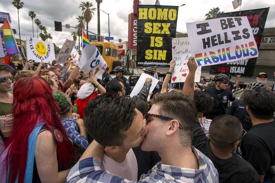 Men kiss in defiance of a counterprotest from street preachers during the L.A. Pride Parade that turned into a ResistMarch. Photo: David McNew, Getty Images