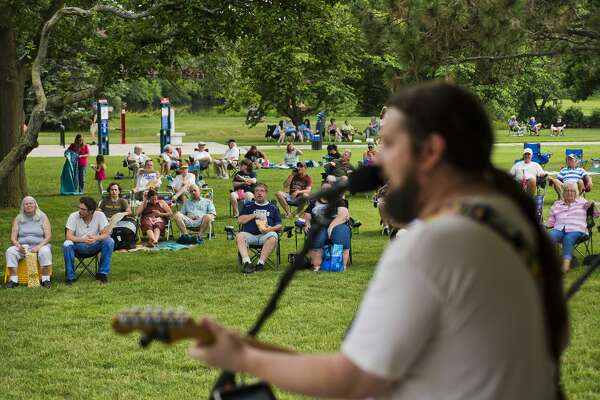 """Dave Miller, lead singer of mid-Michigan band The Etceteras, sings a cover of """"Stuck in the Middle with You"""" by Stealers Wheel with the rest of his band during Tunes by the Tridge on Thursday in Chippewassee Park."""
