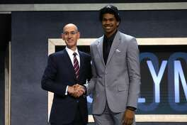 NEW YORK, NY - JUNE 22:  Jarrett Allen walks on stage with NBA commissioner Adam Silver after being drafted 22nd overall by the Brooklyn Nets during the first round of the 2017 NBA Draft at Barclays Center on June 22, 2017 in New York City. NOTE TO USER: User expressly acknowledges and agrees that, by downloading and or using this photograph, User is consenting to the terms and conditions of the Getty Images License Agreement.  (Photo by Mike Stobe/Getty Images)
