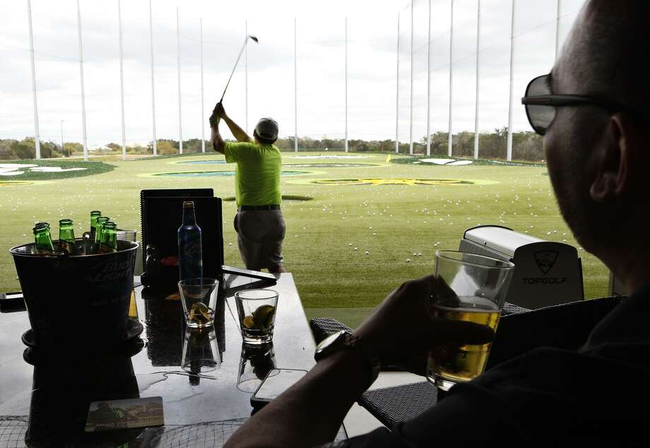 Phillip Covarrubia hits a golf ball as Frankie Covarrubia watches at the TopGolf entertainment complex. Photo: Express-News File Photo / San Antonio Express-News