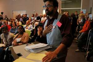 Community members listen as faculty member and librarian Alan D'Souza testifies against the new chancellor pick during a CCSF board of trustees meeting to vote to approve the new chancellor, Mark Rocha, in the multi-use building June 22, 2017 in San Francisco, Calif.