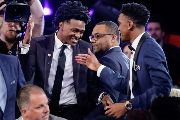 Kentucky's De'Aaron Fox, center in top photo, is all smiles as he heads to the stage to be introduced after being selected fifth overall by the Sacramento Kings in the NBA draft Thursday night.