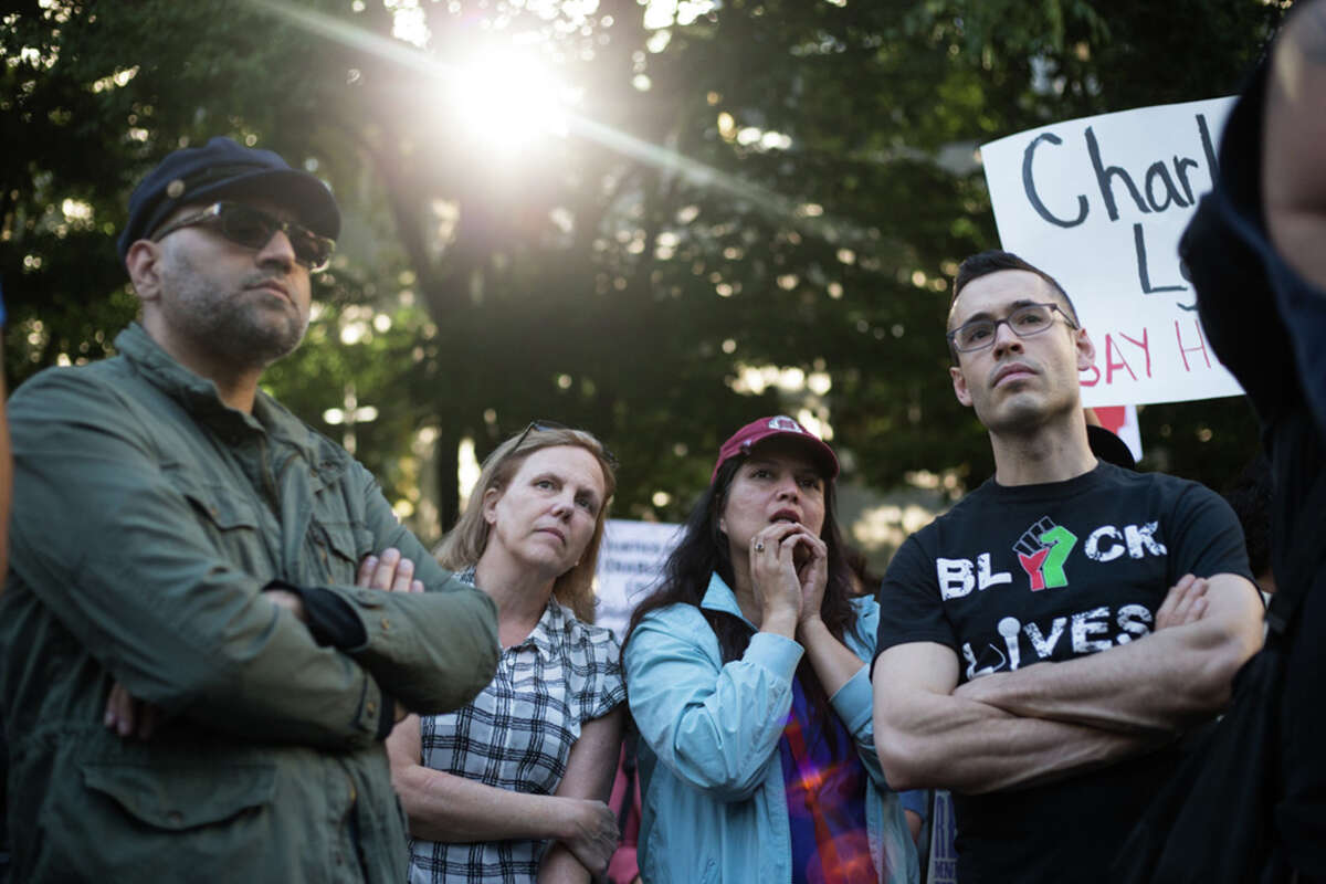 People line up and listen to speakers during a rally protesting the recent police shooting and death of Charleena Lyles, at Westlake Park in Seattle.