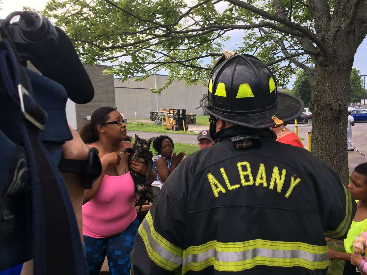 An Albany firefighter hands a cat, just rescued from the North Manning Boulevard blaze, to tearful, overjoyed owner Amber Wilridge on Friday, June 23, 2017. (Emily Masters/Times Union)