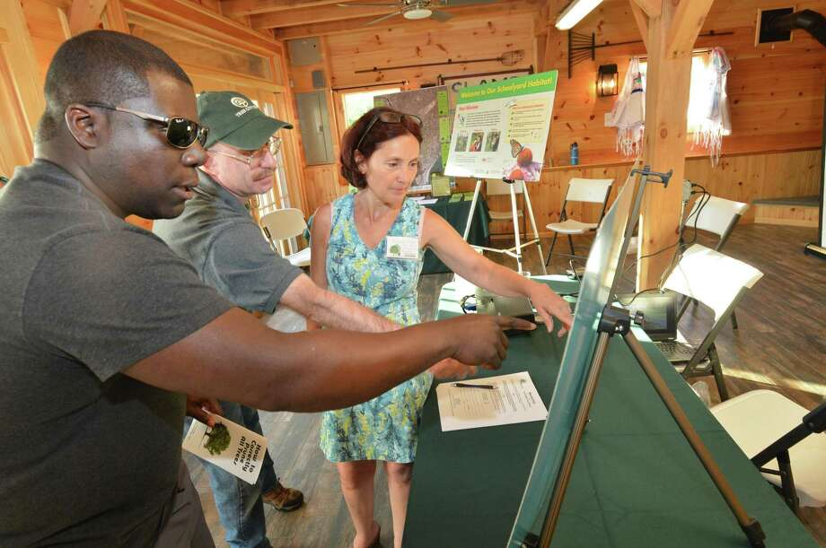 Columbus Magnet Elementary School Principal Medard Thomas looks over a map of the Rosa Parks Arboretum at the school, which has 25 tree species that are native to southern Connecticut. Pointing out some of the specific trees are Paul Sotnik and Yolande LeCoz, of the Norwalk Tree Alliance, during an open house at Fodor Farm on Thursday in Norwalk. Photo: Alex Von Kleydorff / Hearst Connecticut Media / Norwalk Hour