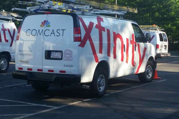 "FILE - In this Sept. 17, 2015, file photo, Comcast trucks are parked in a lot in the company's Westford, Mass. operations center. Cable companies have poured millions into new tools and hires to try to de-agonize the process of getting cable TV, internet or phone service. It's part of a years-long effort to try to assuage customers as the specter of ""cord-cutting"" _ dumping cable for Netflix and the like _ haunts the industry. (AP Photo/Tali Arbel, File)"