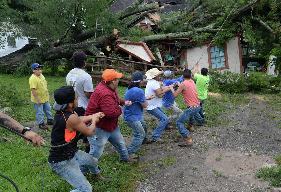 Friends and family help pull a large tree limb from atop a Beaumont home Thursday morning. The tree fell on the home late Wednesday night as Tropical Storm Cindy spun near the coast of the Gulf of Mexico. Family members were in the home during the collapse and no one was injured.   Photo taken Thursday, June 22, 2017 Guiseppe Barranco/The Enterprise Photo: Guiseppe Barranco, Photo Editor