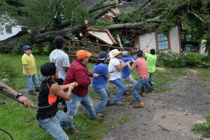 Friends and family help pull a large tree limb from atop a Beaumont home Thursday morning. The tree fell on the home late Wednesday night as Tropical Storm Cindy spun near the coast of the Gulf of Mexico. Family members were in the home during the collapse and no one was injured.   Photo taken Thursday, June 22, 2017 Guiseppe Barranco/The Enterprise