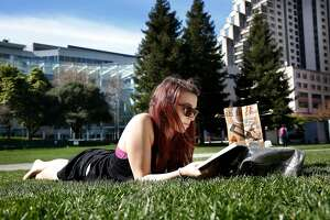 Andrea Glaesmann visiting from Germany reads a book at Yerba Buena Gardens in San Francisco, Calif., during the lunch hour on a warm day on Thursday, February 12, 2015.
