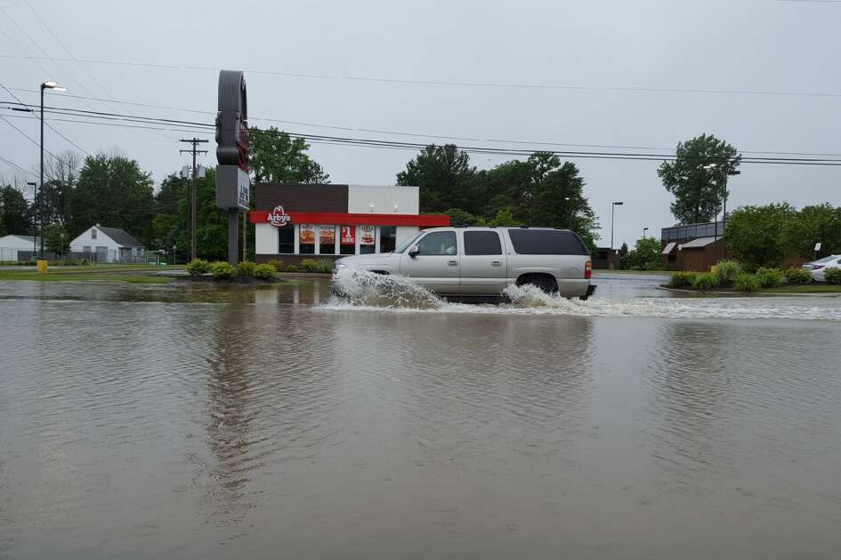 A vehicle drives through flood water on Eastman Avenue Friday morning following an overnight storm that caused flooding in parts of Midland.