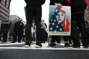 Police stand guard as anti-Trump protesters shout slogans in Washington, DC, on January 20, 2107.� Masked, black-clad protesters carrying anarchist flags smashed windows and scuffled with riot police Friday in downtown Washington, blocks away from the route of the parade in honor of newly sworn-in President Donald Trump.  / AFP PHOTO / Jewel SAMADJEWEL SAMAD/AFP/Getty Images