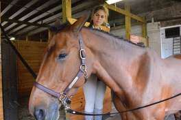Corinne Golan of Fairfield braids Ciara's mane at the Ox Ridge Hunt Club's June Horse Show, Saturday, June 17, 2017, in Darien, Conn.